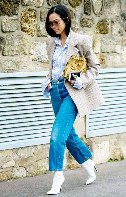С пиджаком в клетку, клатчем с принтом, широкими джинсами и белыми сапогами