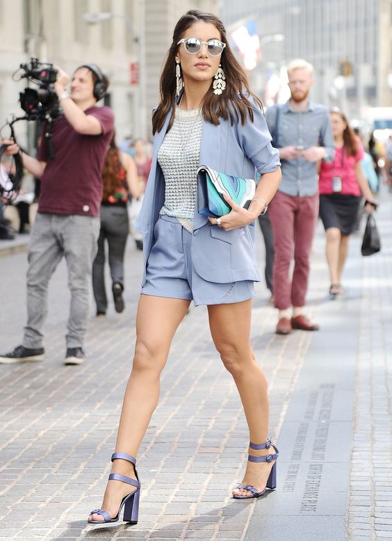 серо-голубой наряд, белый полупрозрачный топ, пестрый клатч, серьги и синие блочные каблуки