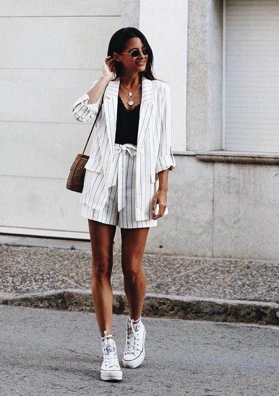 белый негабаритный костюм в тонкую полоску, черный топ, белые кроссовки и удобная сумку для стиля бохо