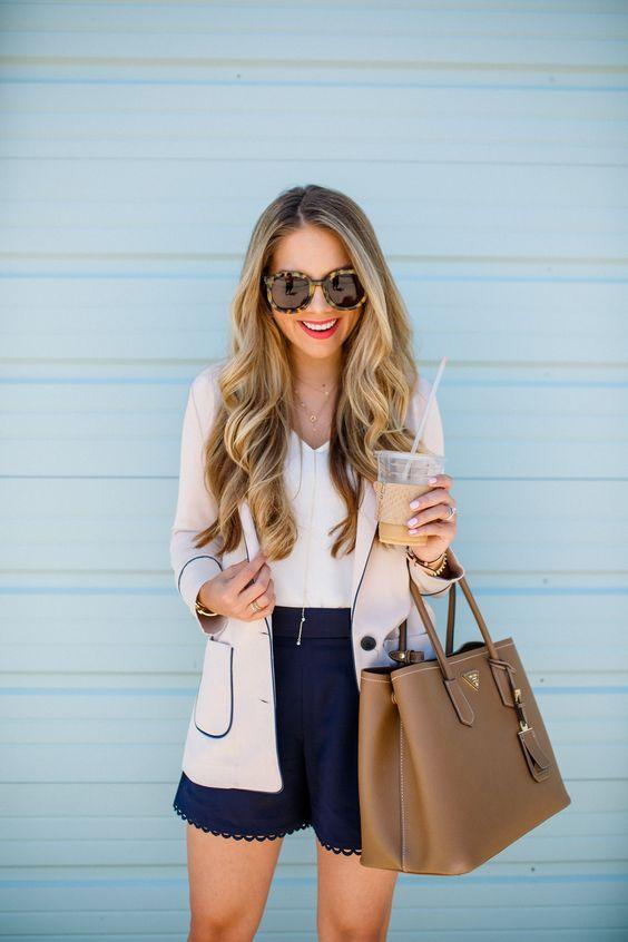 темно-синие кружевные шорты, белый топ с V-образным вырезом, серый и темно-синий пиджак и коричневая кожаная сумка