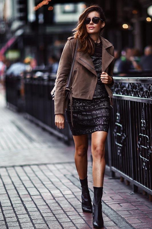 темно-коричневая кожаная куртка с черным нарядным платьем и ботильонами