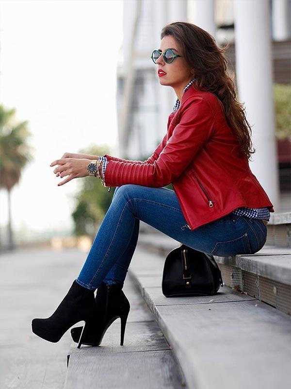 красная кожаная куртка в паре с синими джинсами и темными ботильонами на каблуках