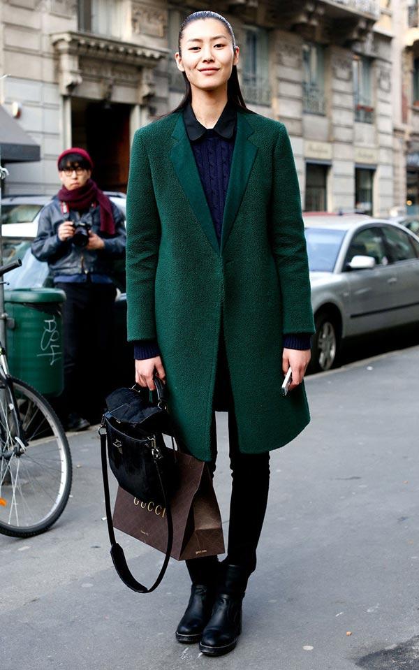 темно-зеленое пальто дополненное синим джемпером, темными брюками, ботинками