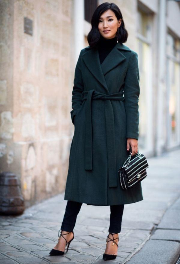 зеленое пальто с черными брюками, туфлями и маленькой сумочкой