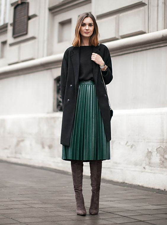 зеленая плиссированная юбка-миди, черный топ, черное пальто и коричневые замшевые ботинки