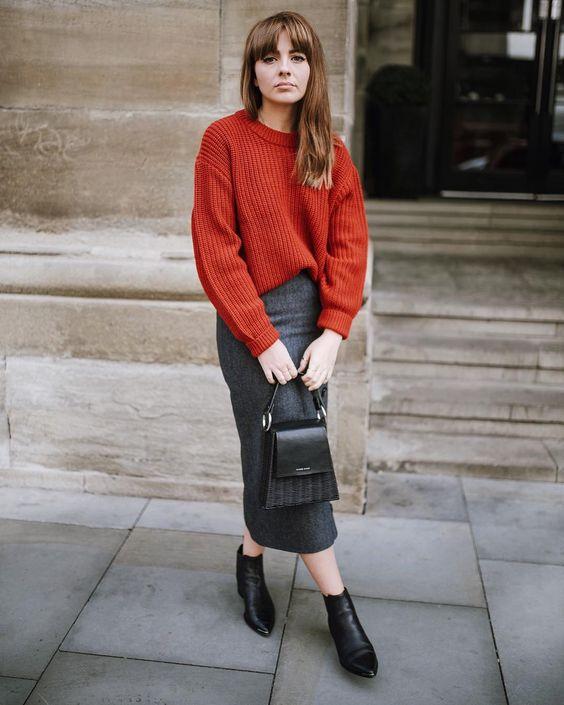 серая юбка-миди, негабаритный оранжевый свитер, черные ботильоны и черная сумка