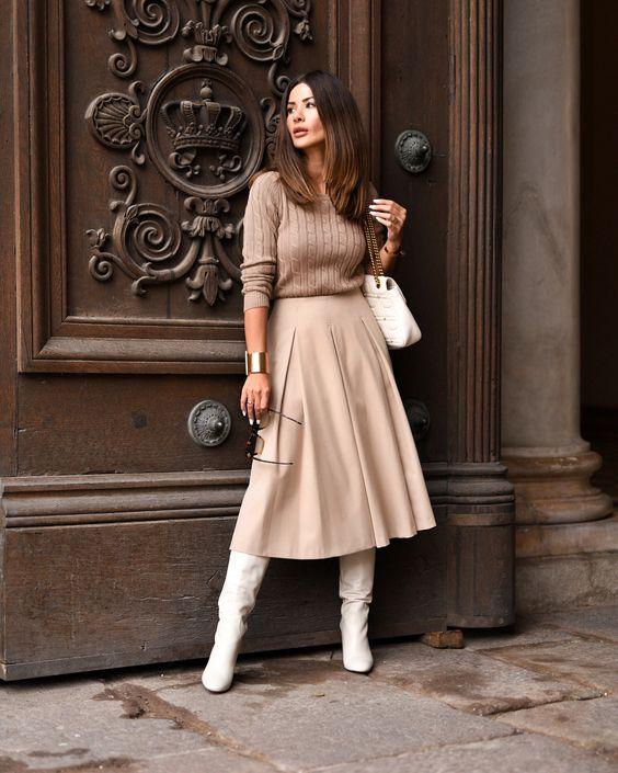 бежевый вязаный вязаный свитер, нейтральные плиссированные миди A-line, белые ботинки, белая сумка привносят романтические нотки