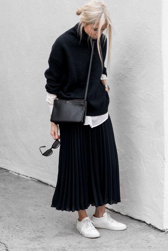 белая рубашка, черный свитер поверх нее, черная плиссированная юбка-миди, белые кроссовки и черная сумка