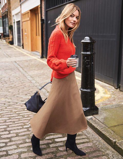 Составьте яркий зимний наряд из бежевой юбки-миди, кораллового свитера, черных сапог и черной сумки