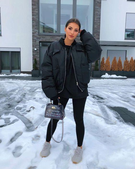 спортивный зимний наряд с черной толстовкой с капюшоном, леггинсы, бомбер с мягкой подкладкой, серые кроссовки и сумка с принтом