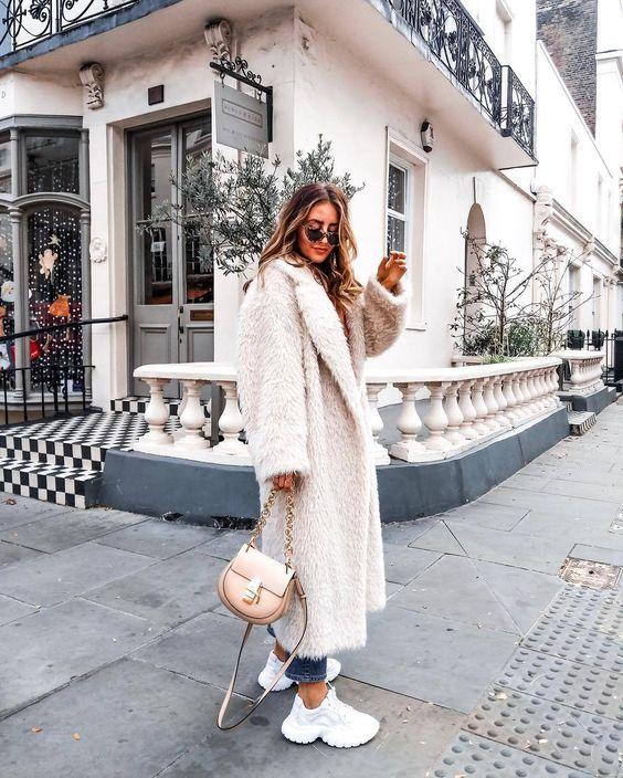 синие скинни, белые кроссовки, белое нечеткое миди-пальто и нейтральная сумка для стильного и удобного наряда