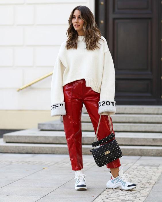 красные кожаные брюки, свободный молочный свите и кроссы