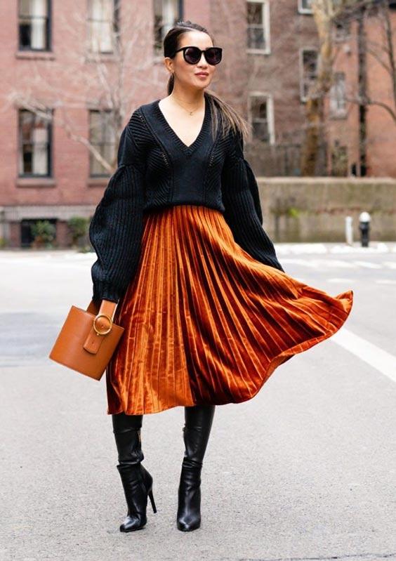 С черным негабаритным свитером, коричневой кожаной сумкой и черными кожаными сапогами