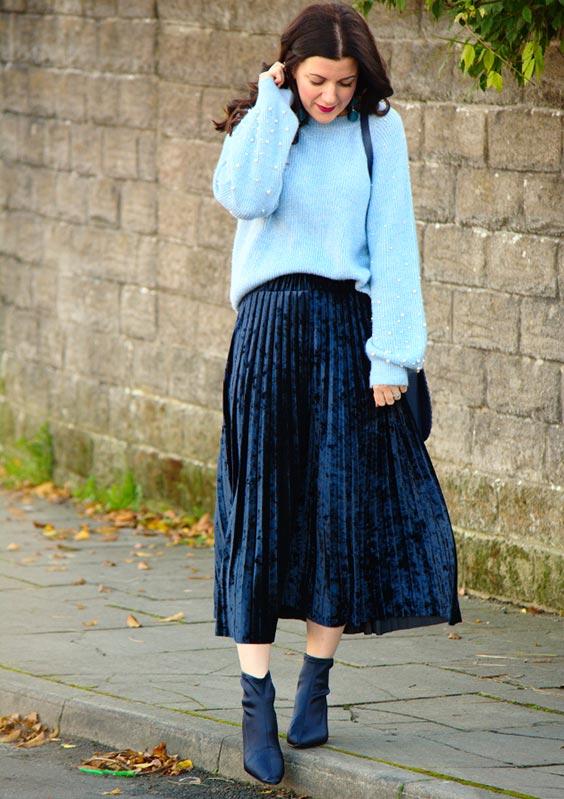 С голубым свободным свитером, сумкой и темно-синими сапогами