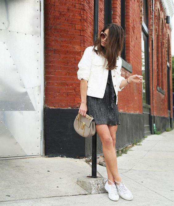 Черное мини-платье, белая джинсовая куртка, белые кроссовки, серая сумка через плечо на лето