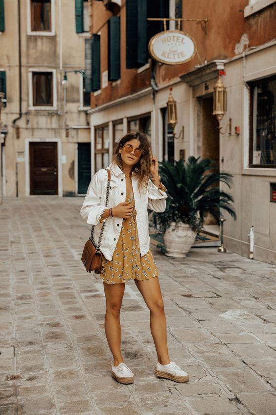Образ с мини-платьем с горчичным цветочным принтом, кроссовками на платформе, белой джинсовой курткой, коричневой сумкой и солнцезащитными очками
