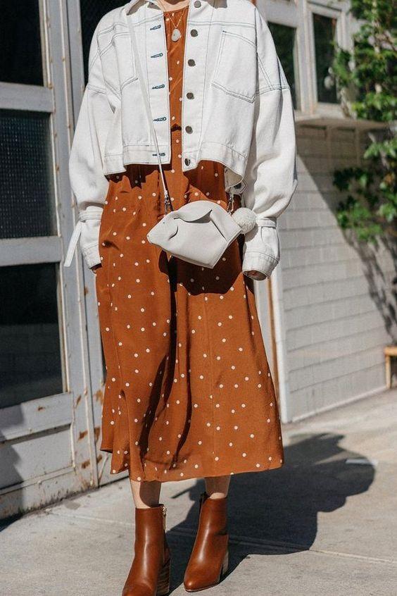 Платье миди цвета ржавчины в горошек, белая джинсовая куртка, белая мини-сумка, коричневые ботинки на весну
