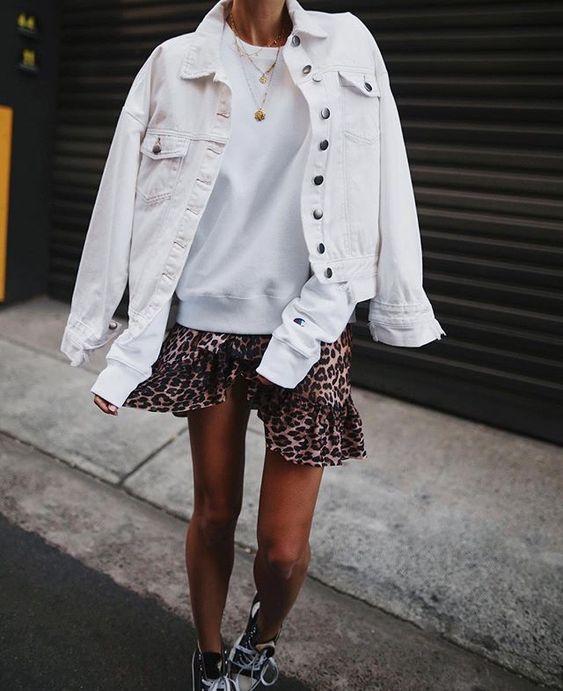 Белоснежный свитшот, мини-юбка с леопардовым принтом, джинсовая куртка, черные кроссовки и многослойные ожерелья