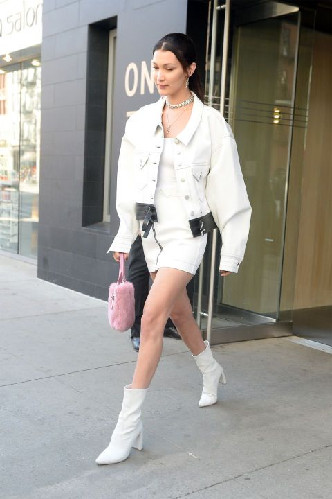 Белла Хадид выбрала образ с белоснежным мини-платьем, большой белой джинсовой курткой, светлыми ботинками и розовой сумкой