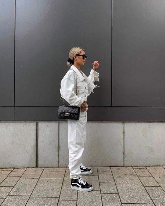 Полностью белый наряд с джинсовой курткой, джинсами, черными кроссовками и черной сумкой через плечо