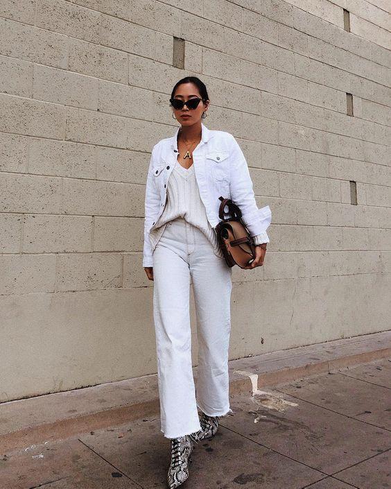 Наряд для девушки с белыми джинсами и джинсовой курткой, джемпером нейтрального цвета, ботинками из змеиной кожи и коричневая сумочкой