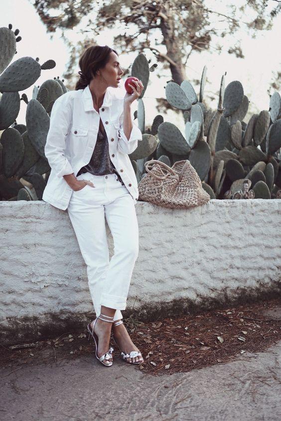 Светлые джинсы в паре с большой белой джинсовой курткой, серой футболкой, серебряными каблуками и тканой сумкой на лето