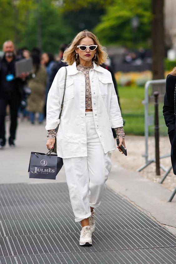 В этом комплекте есть белые джинсы, джинсовая куртка оверсайз, укороченный топ с принтом, белые кроссовки, серая сумка