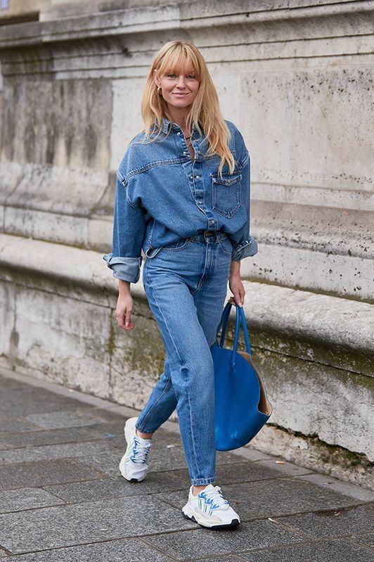 удобный двойной джинсовый образ с рубашкой оверсайз и джинсами, белыми кроссовками и синей сумкой