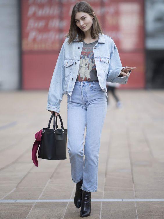 серая футболка с принтом, синие прямые джинсы, синяя джинсовая куртка, черные ботинки, черная сумка на весну