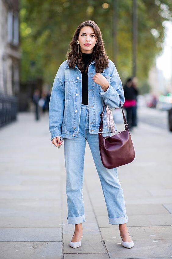 простой женский аутфит с черной водолазкой, синими прямыми джинсами, джинсовой курткой оверсайз, белоснежными туфлями и сумкой бордового цвета