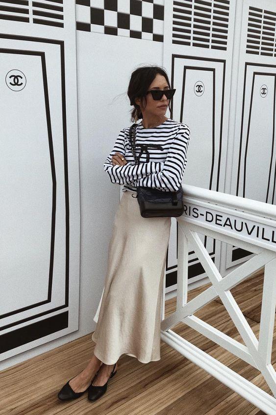 Джемпер в полоску, юбка-миди цвета шампанского, черные босоножки и черная сумка топ в бретонскую полоску, юбка-миди цвета шампанского, черные босоножки и черная сумка