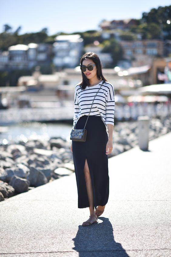 полосатая кофта, темно-синяя юбка-миди с разрезом, черная сумка через плечо и босоножки телесного цвета - отличный вариант для создания образа в морском стиле