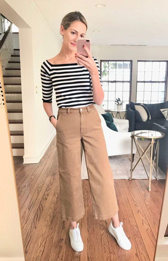 светло-коричневые широкие брюки, полосатый джемпер с короткими рукавами, белые кроссовки для удобного повседневного образа